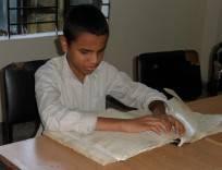 Enfant lisant le Saint Coran en version Braille