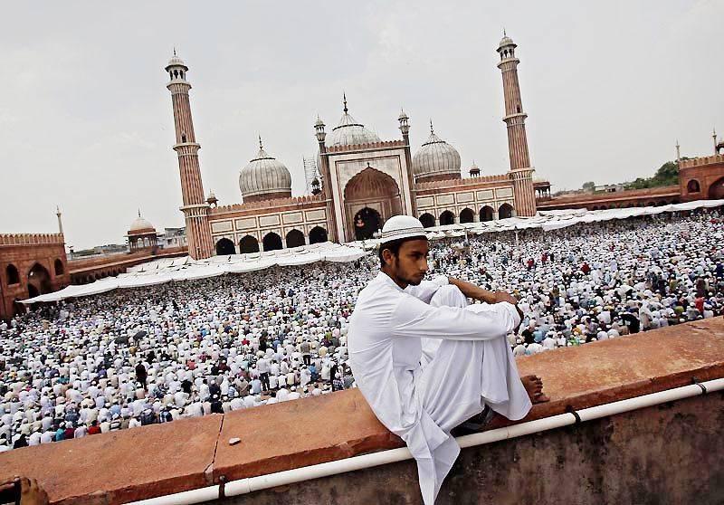 A Muslim man sits on the balcony of the Jama Masjid ahead of Eid-al-Fitr in Delhi