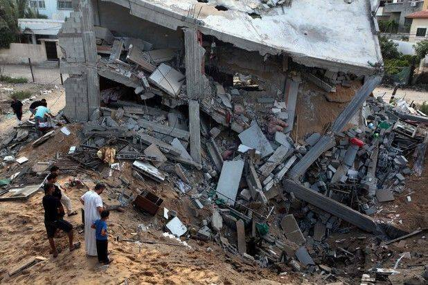 Palestinians gather around the remains of a house which police said was destroyed in an Israeli air strike