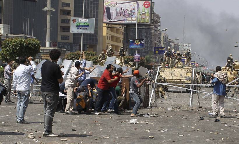 Members of the Muslim Brotherhood and supporters of ousted Egyptian President Mohamed Mursi throw stones at riot police and the army during clashes around the area of Rabaa Adawiya square