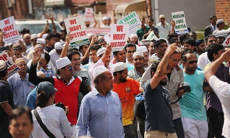 Les gens marchent après la prière janaza pour Imam Akonjee et son adjoint à New York le 15 août.- AFP